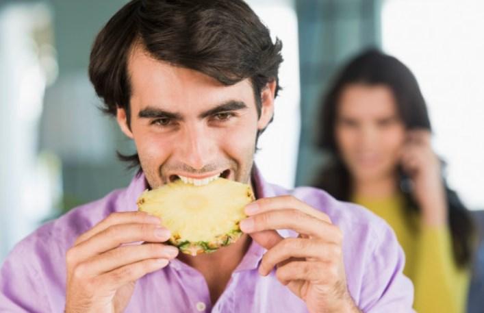 чоловік кусає ананас